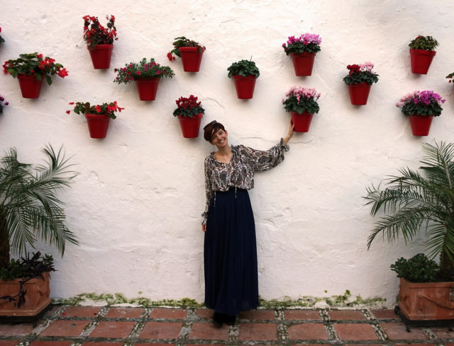 Alicia, Oh My Good Guide Owner, standing by the wall decorated with flower pots