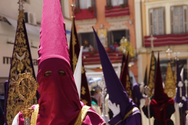 Parade of people wearing pink, purple and red tall masks during Holy Week at Malaga