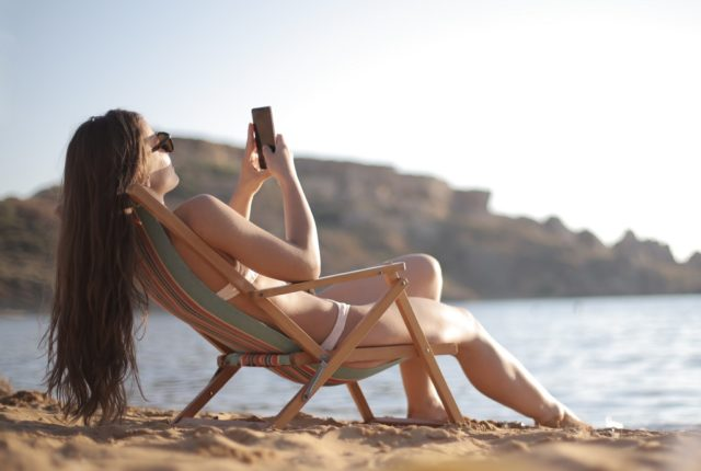 woman using travel apps in spain beach