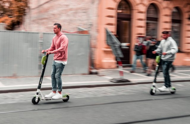 young people driving an electric scooters on the road in Malaga